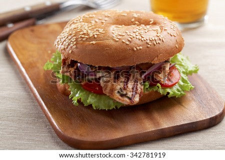 Bagel sandwich with grilled turkey and vegetables - stock photo