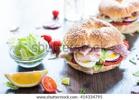 Bagel sandwich with turkey breast and sausage on the table,selective focus  - stock photo