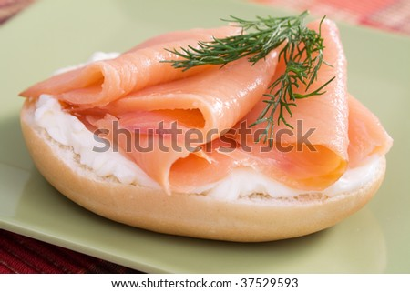 Bagel topped with cream cheese, salmon, and fresh dill. - stock photo