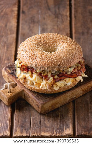 Bagel with bacon, scrambled eggs and fried onion on small wooden chopping board over wooden background. - stock photo