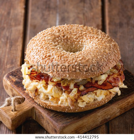 Bagel with bacon, scrambled eggs and fried onion on small wooden chopping board over wooden background. Square image with selective focus - stock photo