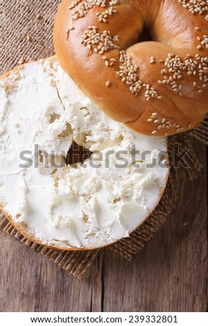Bagel with cream cheese and sesame close-up on a wooden table. vertical top view  - stock photo