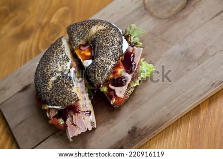 Bagel with ham, salad and cream - stock photo