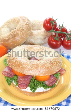 Bagel with salami, peppers, cream cheese and lettuce on white background