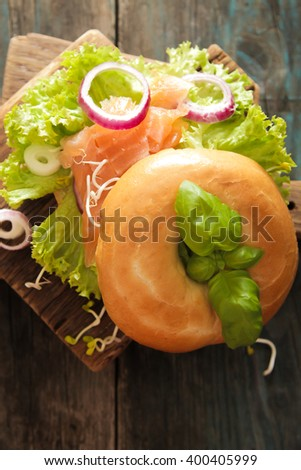 bagel with salmon and germinated sprouts pink salt on a wooden background - stock photo