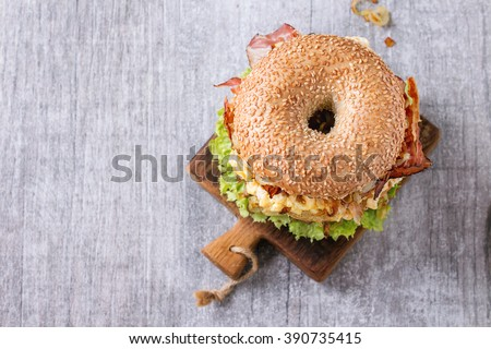 Bagel with stew beef, fresh salad and fried onion on small wooden chopping board over wooden background. Top view - stock photo