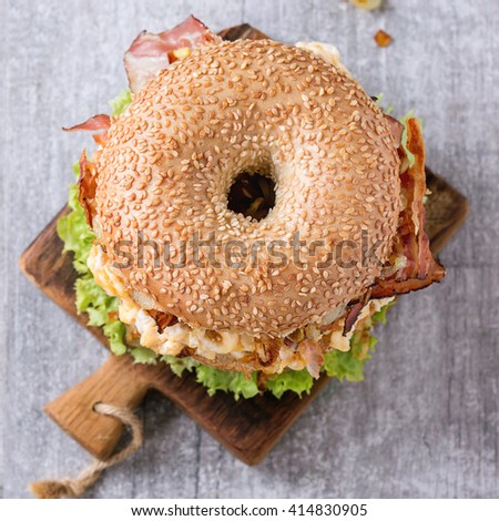 Bagel with stew beef, fresh salad and fried onion on small wooden chopping board over wooden background. Top view. Square image - stock photo