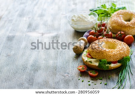 Bagels sandwiches with cream cheese, tomatoes and chives copy space - stock photo