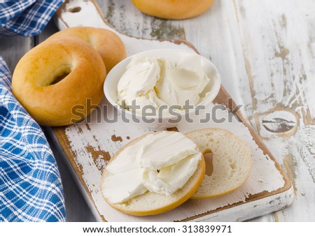 Bagels with cream cheese on  wooden table. Selective focus - stock photo