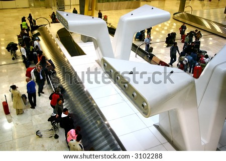 Baggage belt at airport arrival hall showing lots of air travellers waiting to collect their baggages. - stock photo