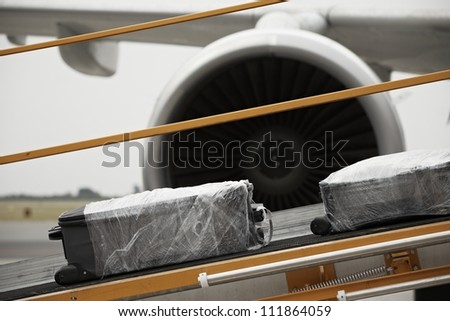 Baggage on the conveyor belt to the airplane. - stock photo