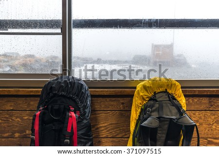 baggage put at window with heavy rain and fog at outside - stock photo