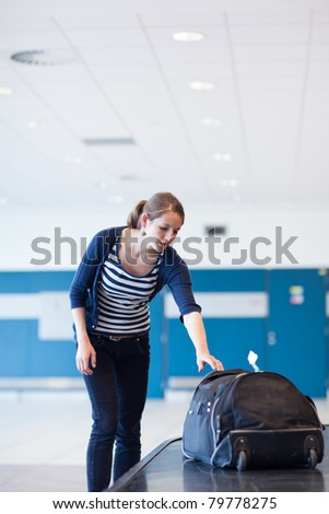 Baggage reclaim at the airport - pretty young woman taking her suitcase off the baggage carousel (color toned image) - stock photo