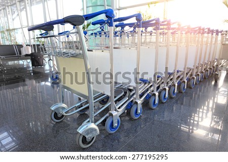 baggage trolley in airport terminal, sunlight from the window - stock photo