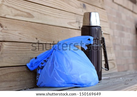 Bagged lunch and a Thermos full of coffee awaits a hungry worker - stock photo