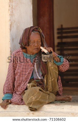 BAGO, MYANMAR - DECEMBER 25: Old woman sits in front of the Buddhist temple on December 25, 2007 in Bago during local religion festival, Myanmar. Woman smokes pretty long and thick cigar. - stock photo