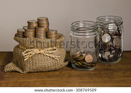 Bags filled with coins on wooden table