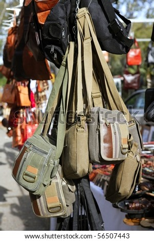 bags hanging in market shop green khaki brown colors