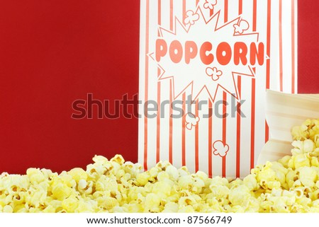 Bags of buttery popcorn against a red background with copy space. - stock photo