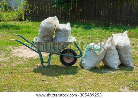 bags of manure in a wheelbarrow - stock photo