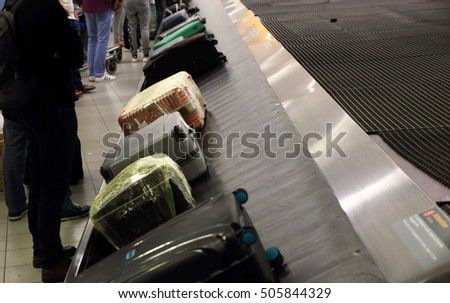 Bags & suitcases on a luggage conveyor belt in the baggage claim at an airport