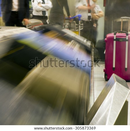 Bags & suitcases on a luggage conveyor belt in the baggage claim at an airport - long exposure - - stock photo