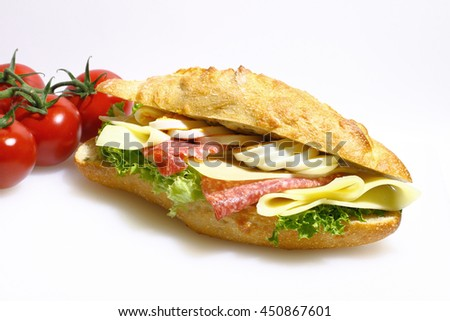 Baguette bun topped with salami, cheese, lettuce and boiled eggs on a white cutting board made of plastic