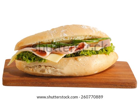 Baguette roll with ham, cheese, lettuce and cucumber slices on a wooden board, isolated - stock photo