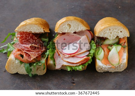 baguette sandwich with salmon and ham,  lettuce and arugula - stock photo