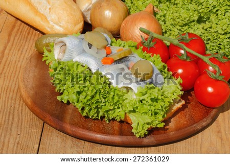 Baguette slices with herring, salmon, pollock, and tuna, garnished and topped with onions, tomatoes, pickles and salad - stock photo