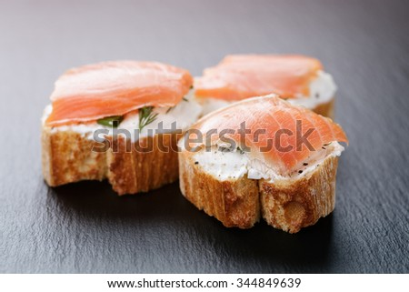 baguette slices with soft cheese and salmon on slate board, vintage toned - stock photo