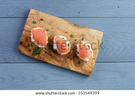 baguette slices with soft cheese and salmon on wood table, from above - stock photo