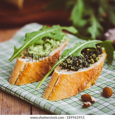 Baguette with green pesto and ruccola leaves. Selective focus. - stock photo