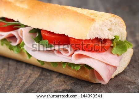 Baguette with ham, cheese, lettuce and tomatoes.
