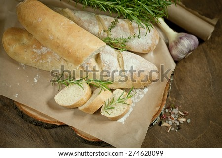 Baguette with Herb and Rosemary on rustic wooden background - stock photo