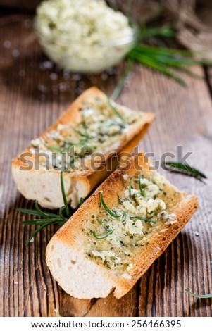 Baguette (with Herb Butter and Garlic) on rustic wooden background - stock photo