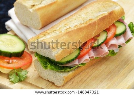 Baguette with lettuce, ham, tomato and cucumber on a wooden board - stock photo