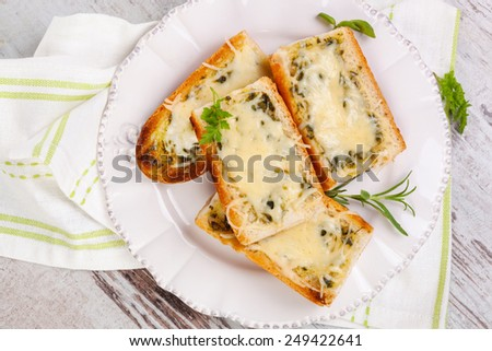 Baguette with melted cheese and fresh herbs on white wooden background, top view. Culinary eating. - stock photo