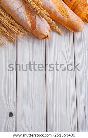 baguettes and croissant wheat ears on wooden boards with copyspace  vertical version  - stock photo