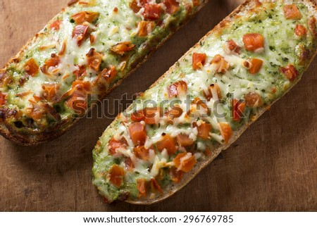 Baguettes with pesto on rustic background - stock photo