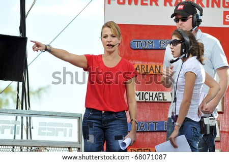 "BAHAMAS, CARIBBEAN - DECEMBER 4:  ESPN's  ""SportsNation"" television show host Michelle Beadle (L), with film crew members, broadcasts live on Dec. 4, 2010 on location at Paradise Island in the Bahamas, Caribbean. - stock photo"
