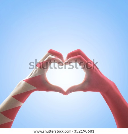 Bahrain flag pattern on people hands in heart shape on vintage blue sky background, symbolic sign language expressing love, unity, harmony of people in country/ nation: Happy National day concept