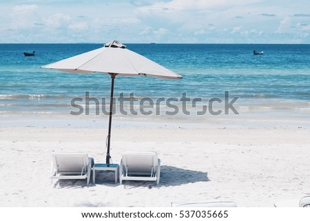 Bai Sao (Star Beach) in Phu Quoc with parasol and two sun bathing chairs on white sandy beach and clear blue water.