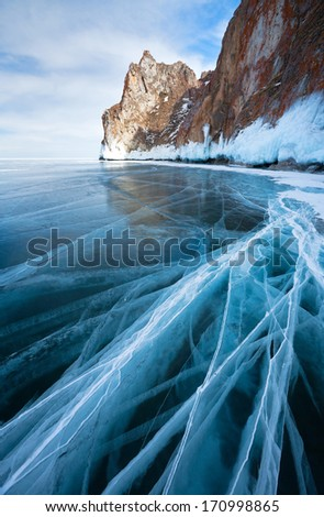 Baikal Lake in winter. Blue ice with cracks - stock photo