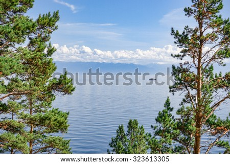 Baikal lake through the trees. Water landscape with ship, moderate mountains and light clouds on the horizon. Framed with green pine branches. - stock photo