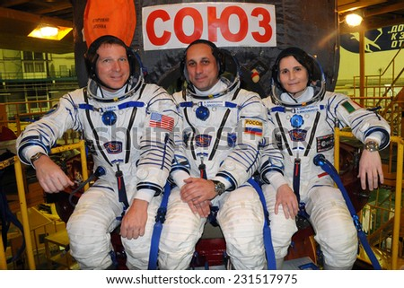 BAIKONUR, KAZAKHSTAN - NOVEMBER 12, 2014: Expedition 42-43 ISS crew (L-R: T.Virts, A.Shkaplerov, Samantha Cristoforetti) pose for pictures in front of their Soyuz TMA-15M spacecraft.  - stock photo