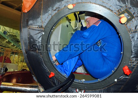 BAIKONUR, KAZAKHSTAN - NOVEMBER 12, 2014: ISS Expedition 42-43 NASA flight engineer Terry Virts in the hatchway of the Russian Soyuz TMA-15M spacecraft during fit check at Baikonur Cosmodrome - stock photo