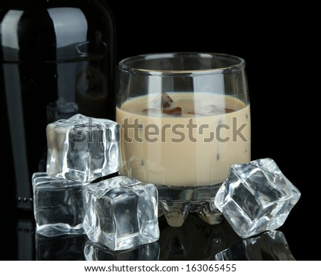 Baileys liqueur in bottle and glass isolated on black - stock photo