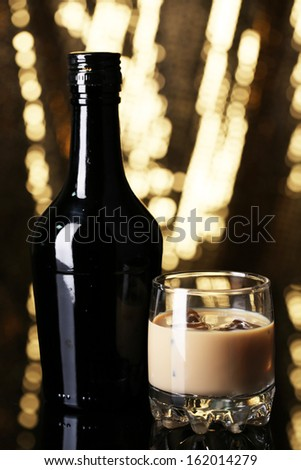 Baileys liqueur in bottle and glass on golden background - stock photo