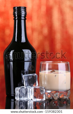 Baileys liqueur in bottle and glass on red background - stock photo